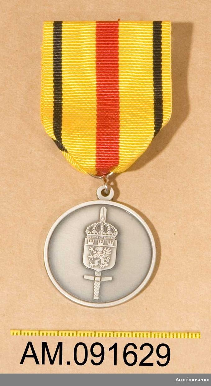 Etui innehållande medalj. MiloMSMM.  På framsidan ett vapen och på baksidan text. Band i gult med bred röd rand på mitten och en svart rand på vardera sidan.