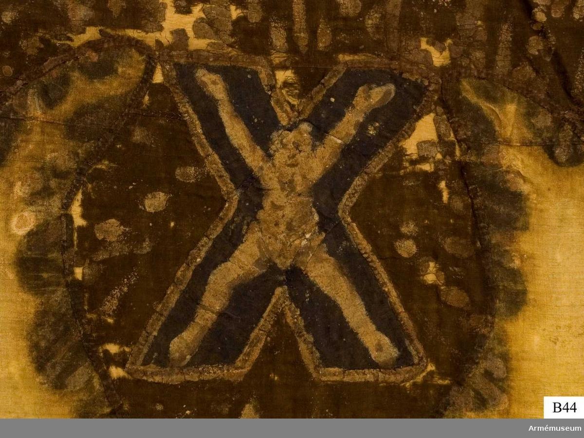 """Gul flagga med ryska dubbelörnen målad i svart och rött, hållande fyra kartor i vitt med blått markerande de fyra haven som Ryssland nått fram till. Infällt i örnens mitt, St Georgsskölden på röd flaggduk. Under örnen infällt i blå flaggduk St Georgskorset. Lik av grov, halvblekt lärft. På flaggan fästes 1790 en etikett av pergament som nu förvaras i Trofésamlingens arkiv. Där står: """"Denna ryska flaggan, 8 duk, är tagen uti Bataillen vidh Svensksund, under Hans Kongl Maijts höga Befäl och Anförande den 9 Julij år 1790. No 1."""""""