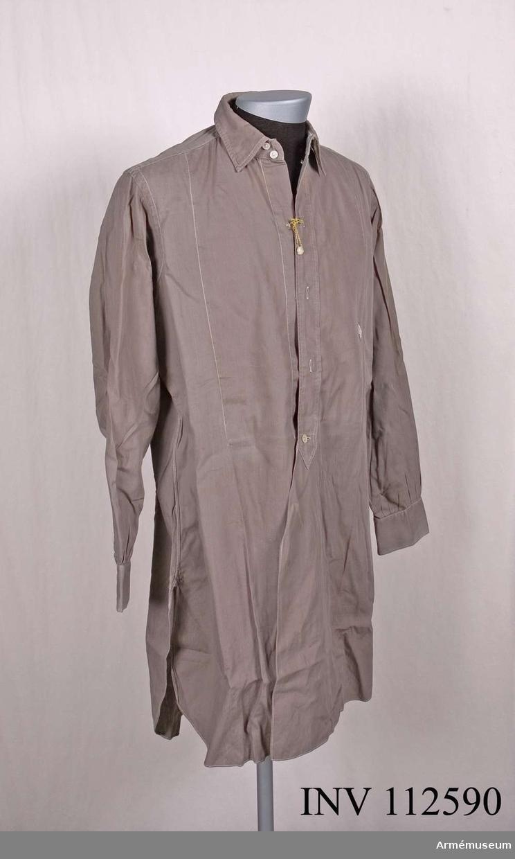 Skjortan har Nordiska Kompaniets etikett fastsydd i kragen. På vänster sida är ett romb-format tygmärke med initialerna FB fastsytt.