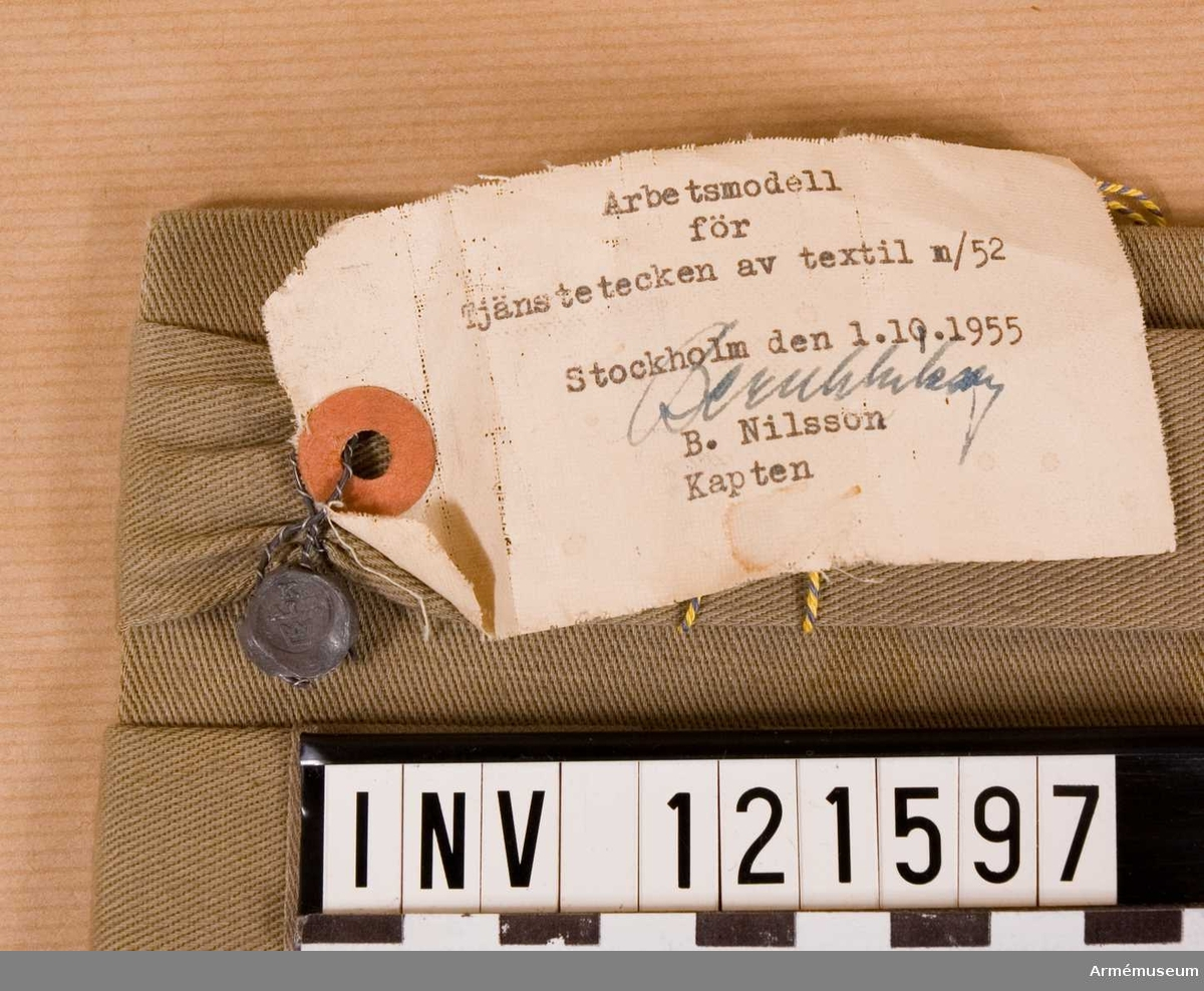 """På modellapp som har sigill med """"Tre Kronor"""" står:  """"Arbetsmodell  för Tjänstetecken av textil m/52 Stockholm den 1.10.1955 [SIgnatur] B. Nilsson Kapten"""""""