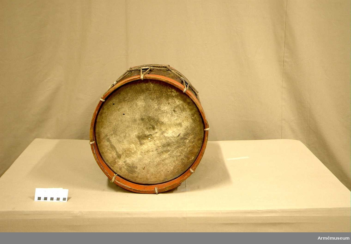 Cylindertrumma av metall, präglade dekorationer. Det ser ut som den ljusa metallen bestrukits med något för att se mörkare ut.   Veckelgjordar: av trä målade med kraftigt röd färg. Nedre v.-gj. fyrkantigt hål ca 2 X 2,5 cm. under sejarhållaren.  Membran: 2 stycken. Det övre är lite buckligt och har några vita små färgfläckar och två små hål. Det undre skinnet är konserverat 1947 står skrivet på pergament eller preparerat papper. Det undre är småprickigt med små bruna färgfläckar och två små hål. Skinnen har småsprickor på ett antal ställen vid spännringarna.  Spännlina: sitter som den skall. Sju vitkalkade spännstroppar sammanfästa med rep och smala läderband. Skarvarna på stropparna är vända in mot cylindern.  Utsmyckning: är rikt dekorerad, med vapensköld.  Bärring: saknas   Märkning: ST TRUMMA 38 med vita tecken direkt på cylindetrn.  Sejarhållare: finns.