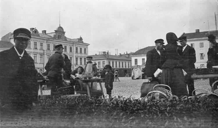 "Bilden var uppklistrad på ett A4 papper. På papperet under bilden stod följande handskrivna text: ""Uddevalla. Torghandel omkr. 1900 - 05""."