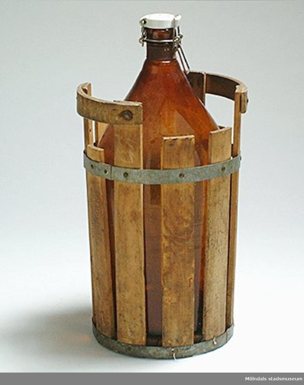 Hållare för flaska i trä. Tillverkad av 10 trälaggar, 4,5 cm breda - sammanhållna av två fastspikade metallband. Två handtag. Botten av rund skiva med utsågat hål - bred spricka tvärs över. Inbränd stämpel på sidan: Eriksbergs Bryggeri. Eriksbergs Bryggeri startades av bryggaren O. A. Andersson på Mölndalsvägen.Tillverkad på 1900-talet. Glasflaska; Mölndals stadsmuseums föremålsnummer 00012-1