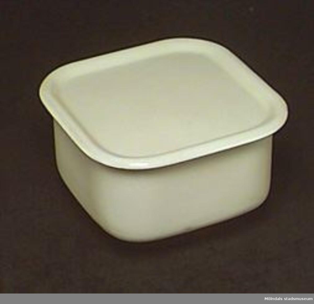 """Burk med lock i grön emalj, från 1950-talet.  Märkt i botten och under locket: Kockums, Sweden, 13 cm, 1 lit. I burken ligger en sexkantig etikett med texten: """"GENUINE KOCKUM SWEDISH SUPER QUALITY ENAMELLED WARE"""".Har använts för förvaring av mat."""