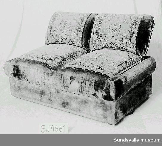 Soffa, tvåsits utan armstöd, klädd i ljusröd och grå plysch med blommönster. Snörmakerier. Ställbara ryggstöd. Hjulförsedda ben.  Enligt anteckning så anskaffades möbeln efter branden 1888 i Sundsvall. Jfr. SuM 0662.