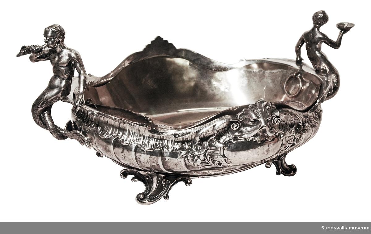 Två silverskålar på fötter med förgyllda löstagbara innerskålar, vilka är försedda med ringar att lyfta i. Skålarna är dekorerade med mytologiska figurer (sagofigurer?) och maskaroner. Gravyrfält. Nyrokoko  SuM 2333:1 är 49 cm lång och 20 cm bred. G SuM 2333:2 är 48 cm lång och 21 cm bred. Skålarna är stämplade med 'C.G. HALLBERG', 'kattfoten' och Stockholms stads stämpel.
