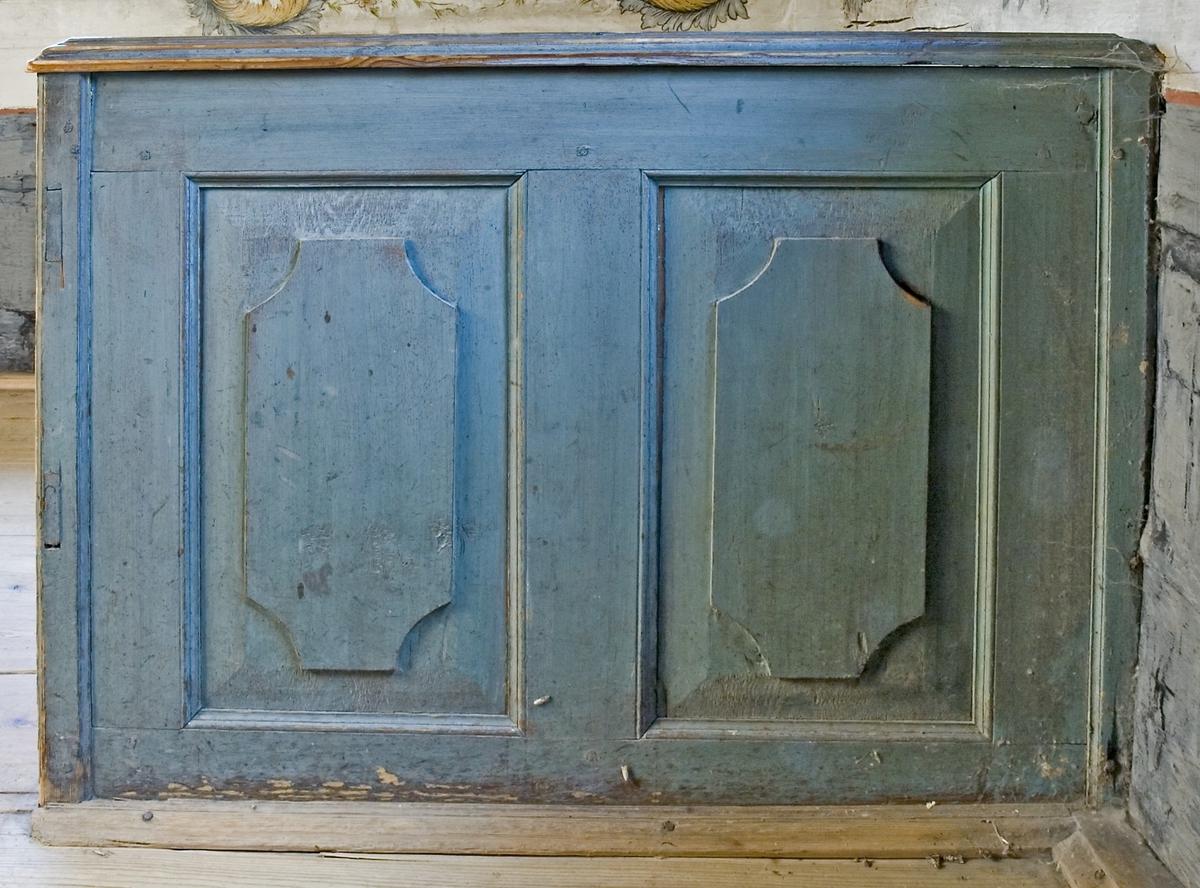 Säng av trä, målad i blått. Platsbyggd. Fotänden upphöjd, med profilerad krönlist. Gaveln med två speglar, profilerade. Långsidan med svängd överkant, därunder en profilerad list. En liten bit profillist, liknande ett lock, placerat på inre kortsidans yttre hörn. Både tränaglar och järnspikar har använts vid hopsättningen.