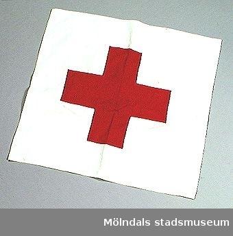 Vit flagga med rött kors för markering av Röda Korsets verksamhet. Har använts av Karin Örtlund som var Röda Kors-instruktör. Hör ihop med: Uniform MM02155:1-3.