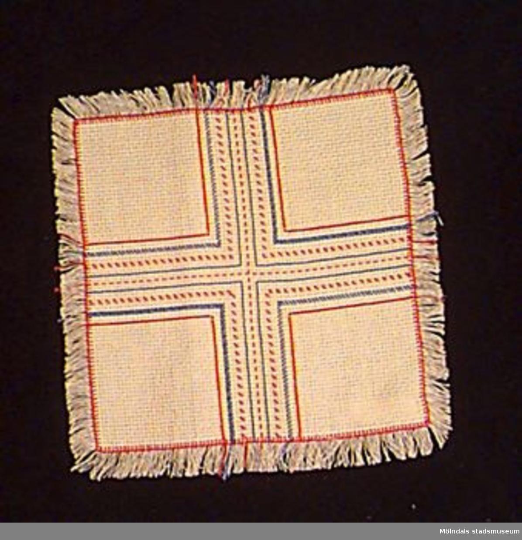 En vävd duk med fransarna kvar från väven. Gult tyg med broderier i rött och blått. Mönstret utfört som ett kors. Undervisningsmaterial för åk 3 och 4. Samhör med 02653-02661.Övriga uppgifter se 02643:1.