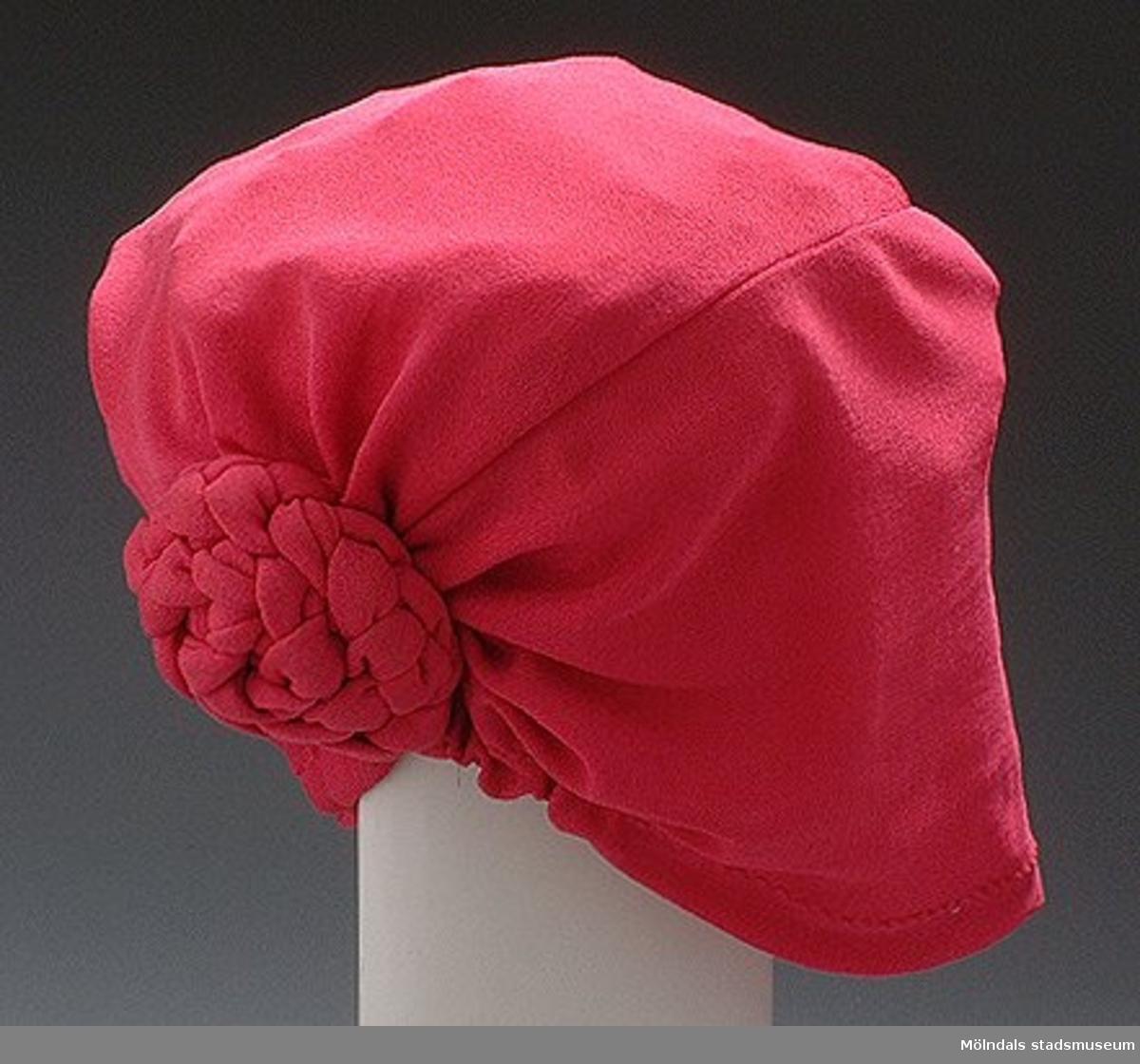 Rosa hatt/mössa med en knut bak på.Det finns också tillhörande blus, kjol och kavaj: invnr. MM03346:1, MM03346:2, MM03346:3.Måtten:Höjd 200 mm, diam. 200 mm.