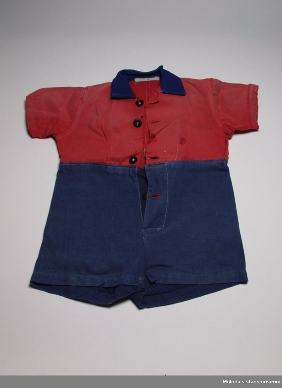 Lekdräkt med korta ärmar och ben. Överdelen är sydd i rött tyg och underdelen samt kragen i blått. Sliten och stoppad.