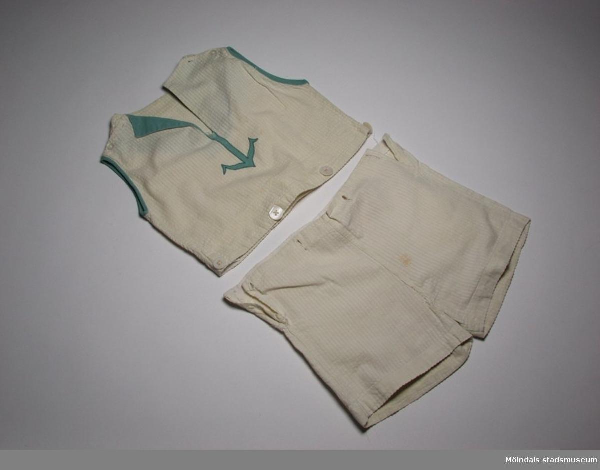 """Lekdräkt i gulvit """"bäck å bölja"""". Korta ben och ärmlös. Blusen har en grön applikation i form av ett ankare.Blus (:1) bredd: 320 mm, längd: 280 mm.Byxa (:2) bredd: 320 mm, längd: 250 mm."""