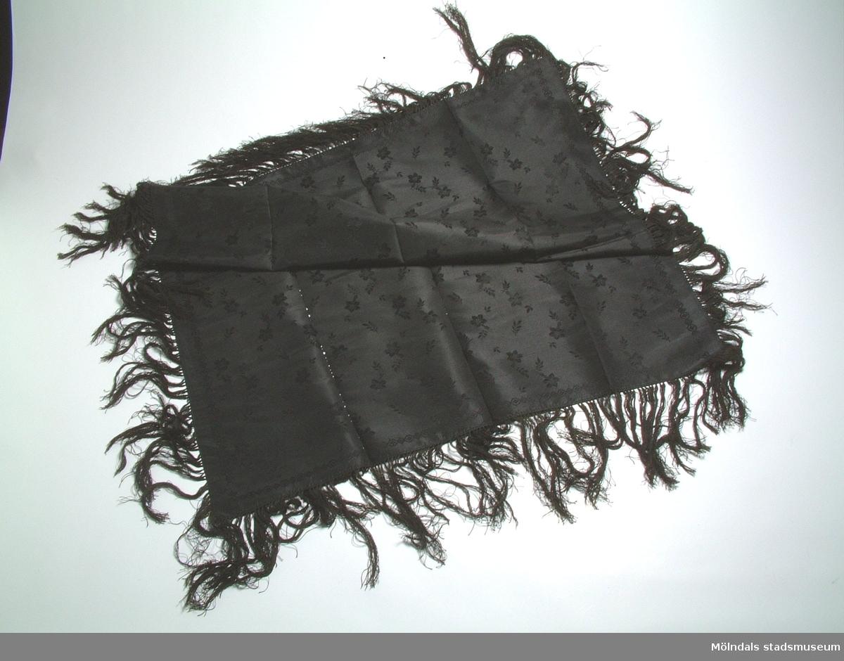 Svart schal med invävt blommönster och en 14 cm lång silkesfrans. Skör, trasig i vikningarna. Schalen har troligen använts av givarens mormor född 1882.
