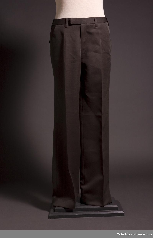 Herrkostym bestående av sandfärgad yllekvaj: 04186-1, grön herrbyxa: 04186-2 samt grön sammetsfluga 04186-3. Kostymen användes av medlemmarna i Mölndals körsällskap.Kören bildades 1925 men upphörde i samband med att Mölndalskören Opus bildades i början av år 2001 genom en sammanslagning av körerna Mölndals Körsällskap och Chorus Prisma.
