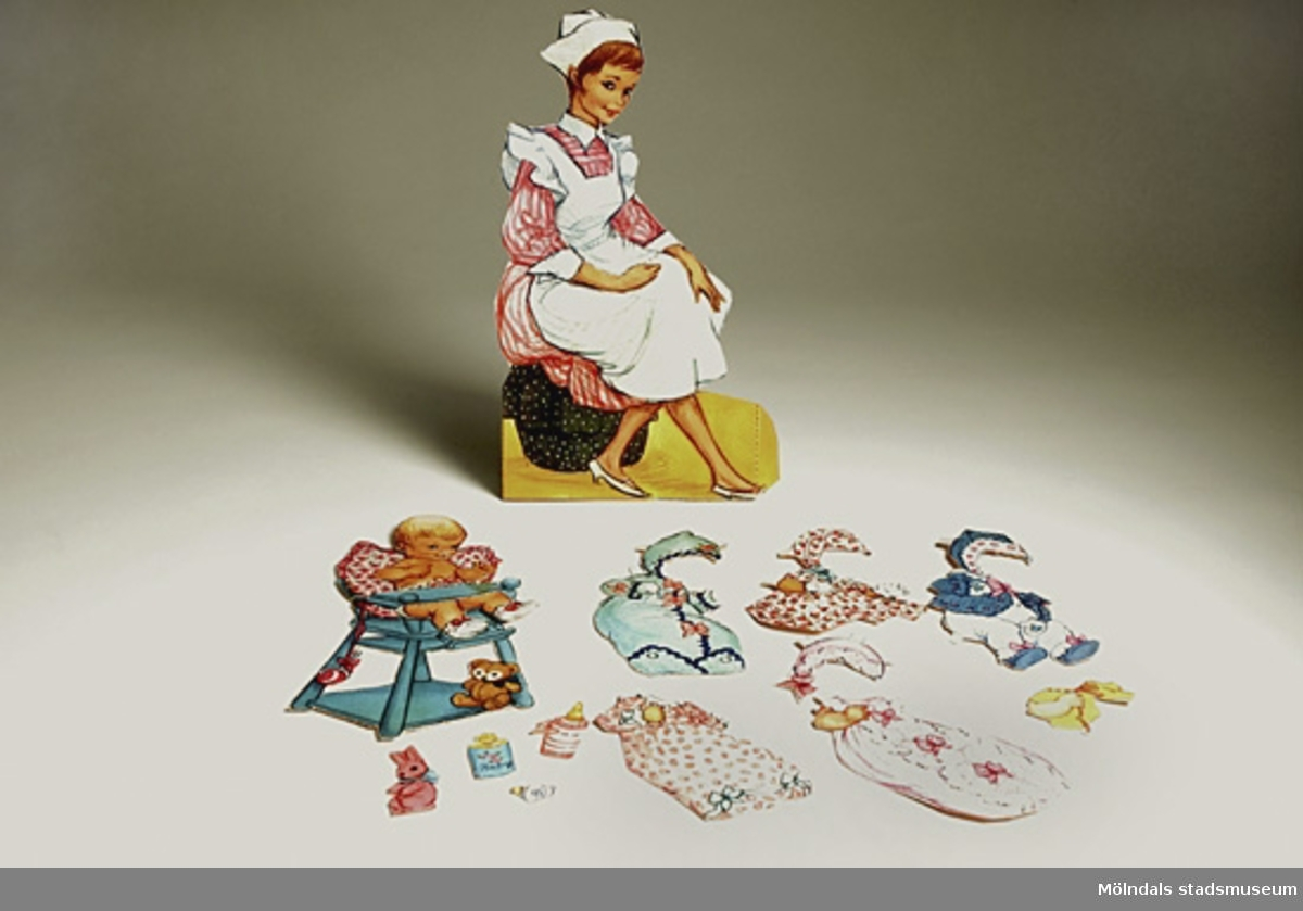 Babyflicka med ljust hår i blöjor (115 mm, 60 mm). En sköterska som kan hålla henne i famnen (240 mm, 190 mm). En hög barnstol (165 mm, 100 mm), och leksaker, samt 13 st. klädesplagg.