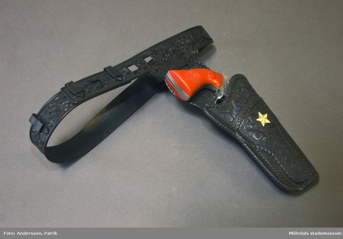 1: Silverglänsande knallpulverpistol. Kolven av röd plast.2: Bälteshållare av svart plast dekorerad med sheriff-stjärna.