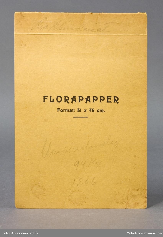 """Häfte med prover """"Florapapper, Format 51x76 cm"""". Pärm av gult papper med tryckt text och en handskriven anteckning i blyerts: """"Bokbinderiet, Universalomslag"""". Varje ark märkt med  siffra, ordnade lättöverskådligt, blommönstrat och julmotiv. Litteratur: Papyrus 1895-1945, Minnesskrift, Esseltes Göteborgsindustrier AB, Göteborg 1945."""