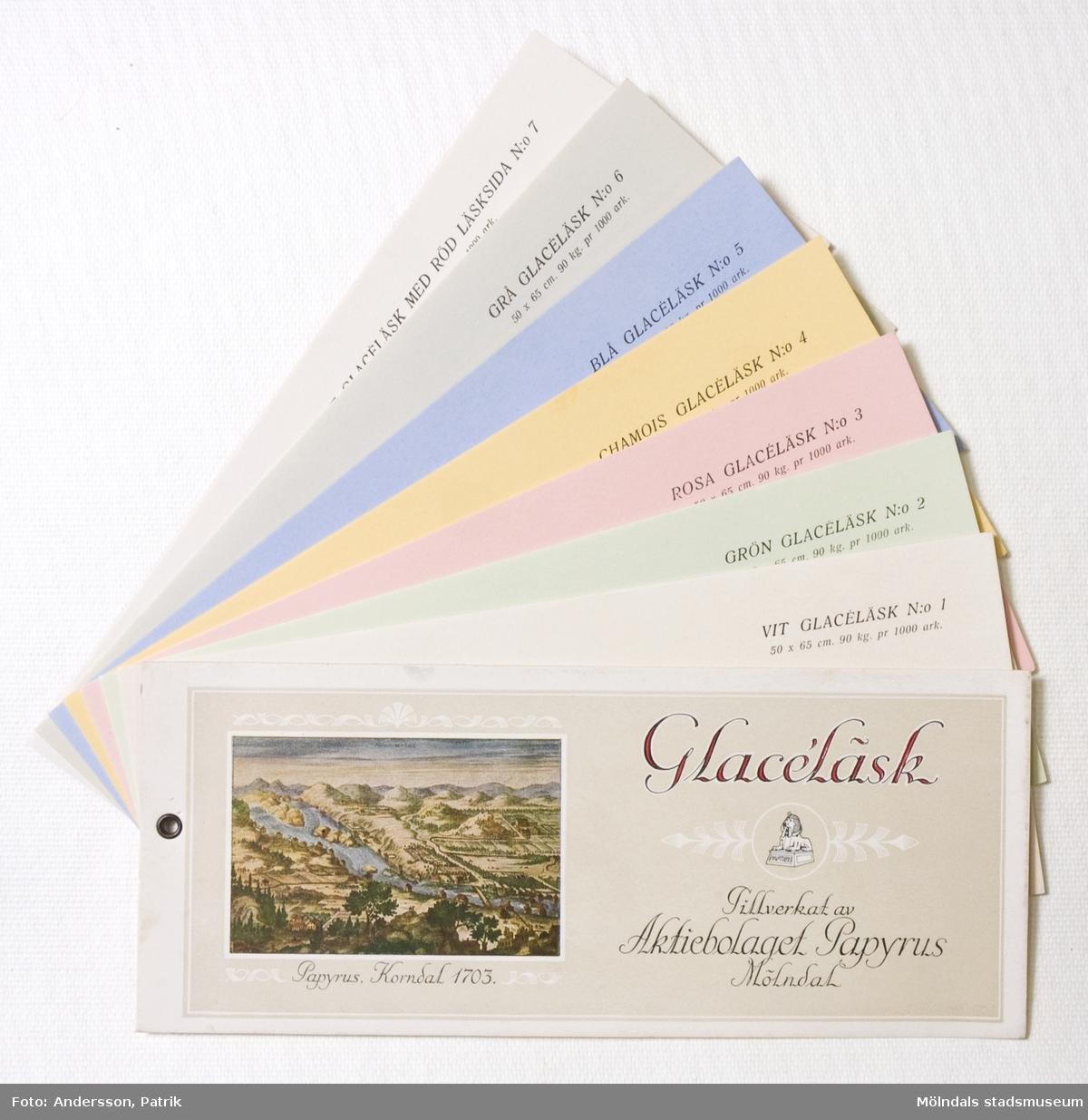 """Häfte med prover, """"Glacéläsk"""". 7 st provblad i ljusa pastellfärger, fästa med nitat hål. På omslaget finns en färglitografi som föreställer Papyrus, Krondal från 1703. Papyrus logotyp och tillverkarnamn. Litteratur: Papyrus 1895-1945, Minnesskrifter, Esseltes Göteborgsindustrier AB, Göteborg 1945."""