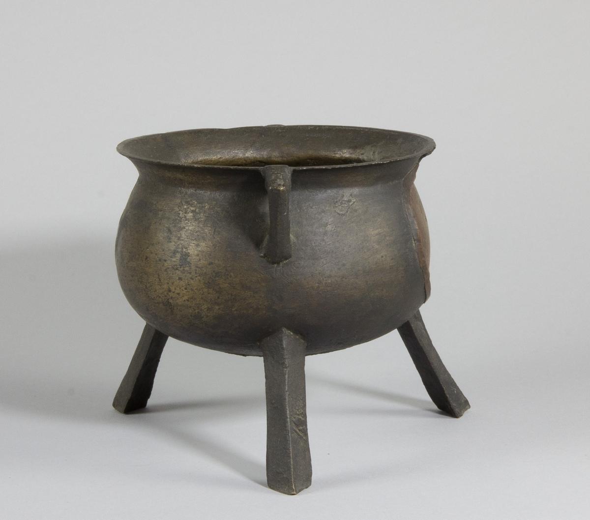 """Gryta av järn. Rund form med utåtstående kant och  flat botten, med två öron och tre fötter. På sidan kartusch av koppar med stämpel: """"1866 S T""""."""