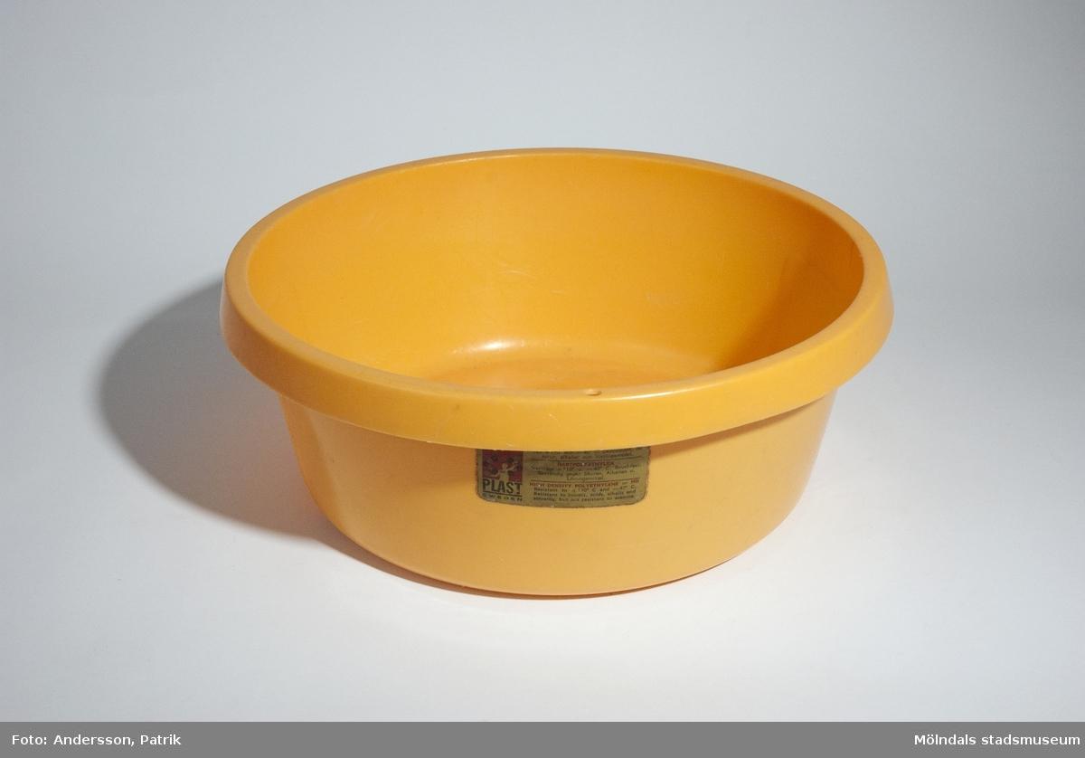 """Gul rund balja som rymmer 6 liter. Den är från 1970-talet.Under baljan i botten finns det gjutet i plasten: Hammarplast-loggan och texten """"DESIGN BREBER    6L"""".På sidan sitt ett guldfärgat klistermärke med Hammarplast-loggan och skötselrådet: """"HÅRD ETENPLAST = HD   Tål +110 (g) och -40 (g). Okrossbart, tål syror, alkalier och lösningsmedel."""", på tre olika språk.Givaren Kerstin använde baljan under 1970-talet.MåttDjup: 120 mm, Diam: ca. 330 mm"""