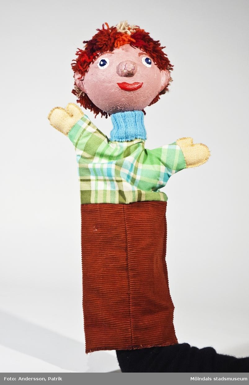 """Hans ur sagan om Hans och Greta. (se 04905). Handdockan har ett huvud av gips, garnhår i grått och olika nyanser av rött, grön-blå-vitrutig skjorta och nederdel av brun manchester. Givaren Blanka Kaplan var förskollärare som använde dock-teater i sin pedagogik. Hon var ledare för dockteatern """"Tusen-sköna"""" som spelade klassiska sagor i tjeckisk tradition. Blanka Kaplan är född i Tjeckoslovakien och kom till Sverige 1968. De sista åren före sin pension åkte hon runt i olika förskolor med sina föreställningar. (se bilaga i arkiv)."""