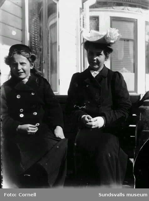 Två unga kvinnor i fina kläder utanför huset på Kaptensudden.