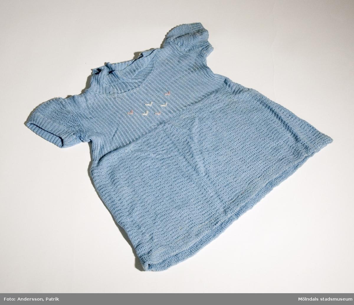 Ljusblå flickklänning. Smått broderat mönster fram.