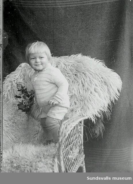Porträtt, baby ståendes  i en stol