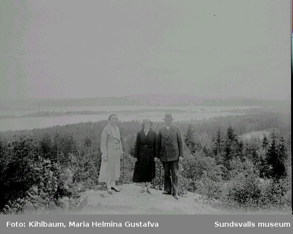 Vy. Man och två kvinnor står på ett berg, hav och fabrik i bakgrunden.