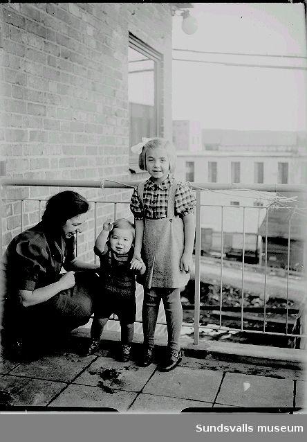 Kvinna med två barn på en balkong.