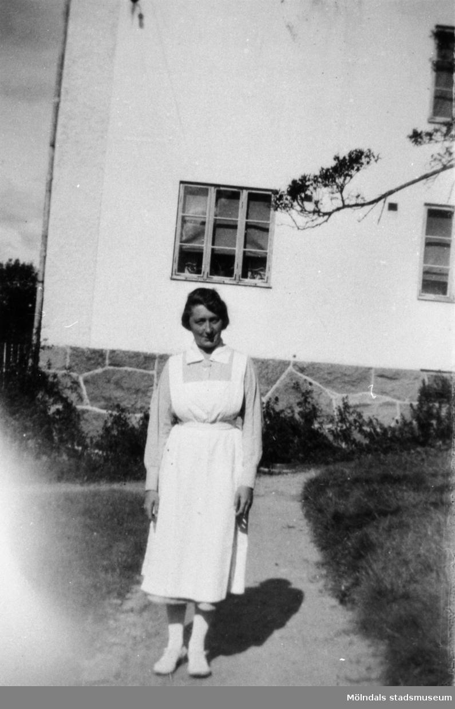 """Anna Hasselberg, vårdarinna på Stretered, står utanför """"Flickornas arbetshem"""". 1940-tal."""
