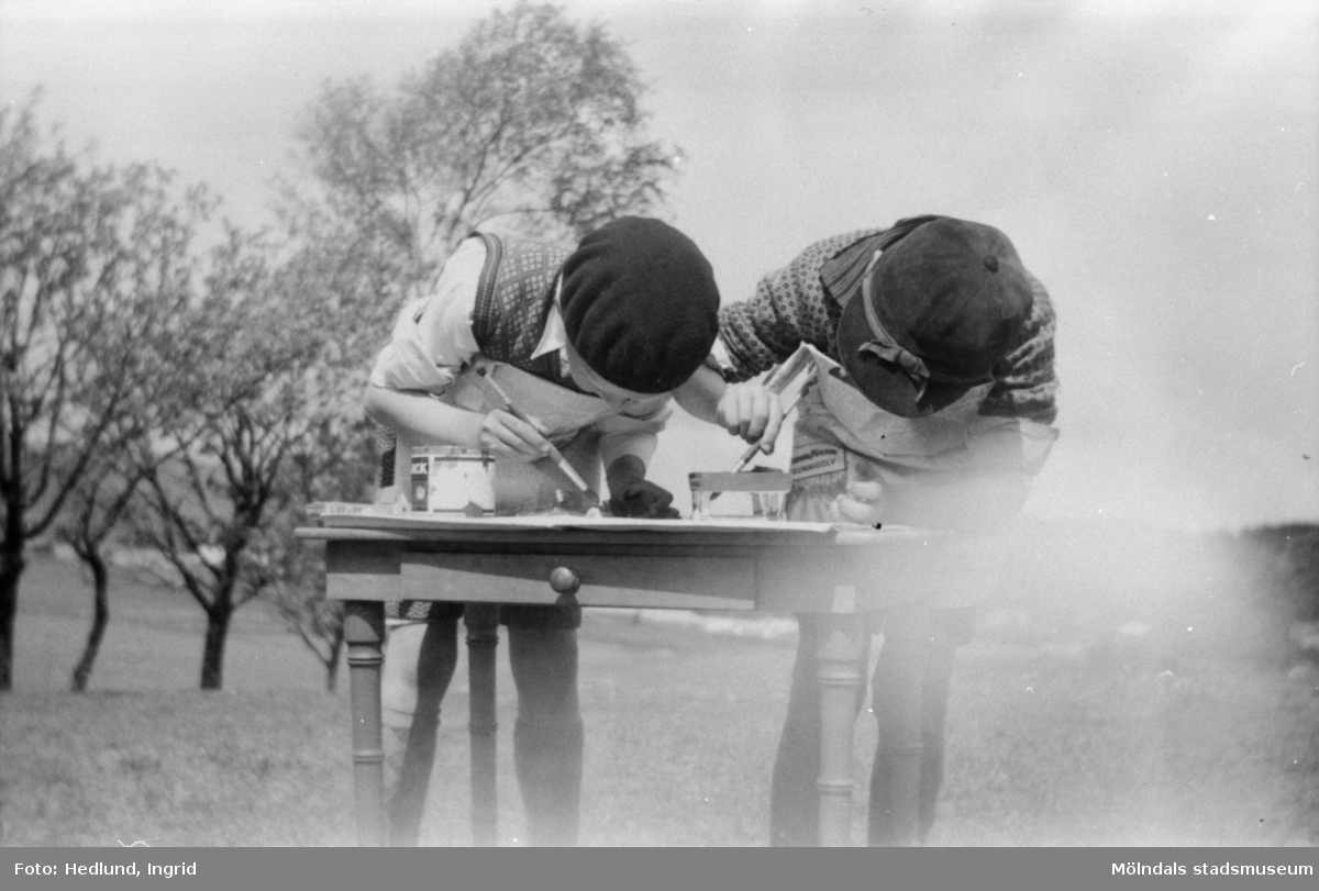 Bosgårdens barnträdgård cirka 1938. Två barn målandes vid ett bord.