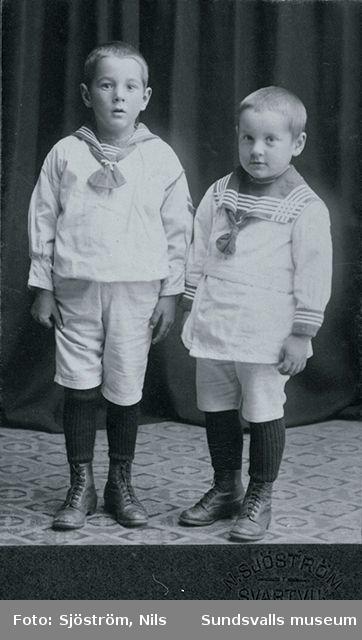 Porträtt av två pojkar i sjömanskostymer. Visitkort med logotyp N. Sjöström, Svartvik.