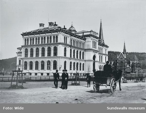 Till vänster i bild Allmänna Läroverket och till höger i bild Skolhusallèn med skolgossar och en häst och vagn.I bakgrunden syns byggnadsställningar uppförda kring Gustav Adolfskyrkan.