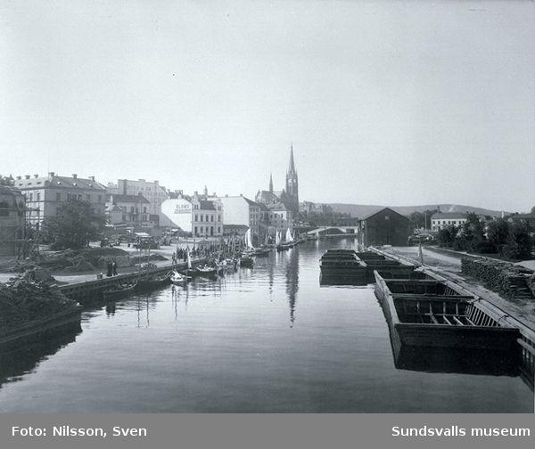 Från vänster Fisktorget, Selångersån med bruksbåtar, magasin. I bakgrunden Gustav Adolfskyrkan.