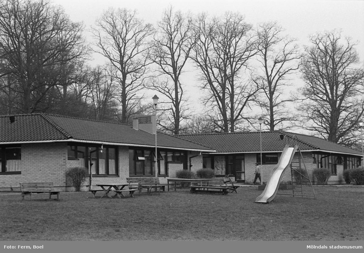 Gruppboende med gräsmatta framför. På gräsmattan står en rutchkana samt sittgrupper. Dokumentation av Sagåsens flyktingförläggning, 1992.