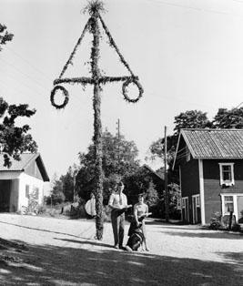 Lantbrevbärare Erik Johansson och Fru V. Andersson, Bammarboda gård.  Den bilåkande lantbrevbäraren Erik Johansson arbetade på linjen Åkersberga-Singö-Björnhuvud-Åkersberga.  Foto augusti 1961.