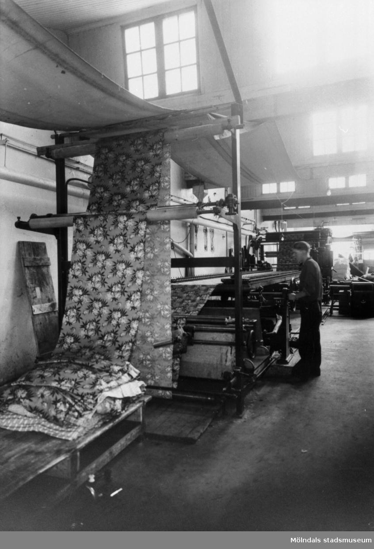 Tyget sträcks och rättas i en av spännramarna i Krokslätts fabrik.