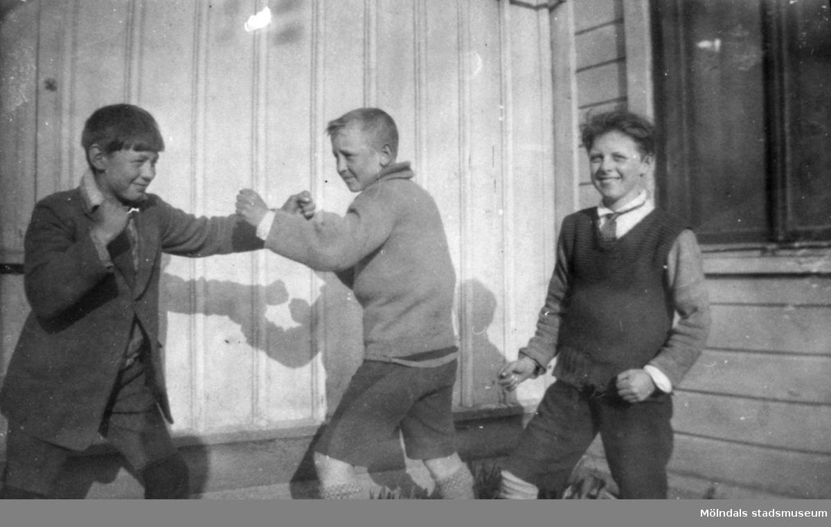 Två killar som låtsas-bråkar och en ung Helmer Garthman längst till höger. 1920-tal.
