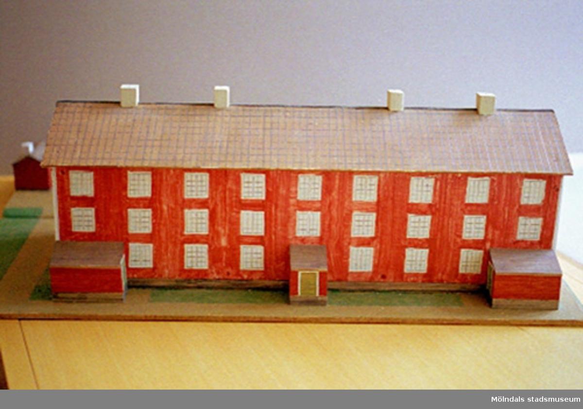 """Ett rött bostadshus med tio fönster i rad, tre våningar högt, och tre entréer. På taket finns fyra skorstenar. Vid sidan av ligger två mindre stugor. Huset är en kopia av """"Byggninga"""" som var arbetarbostäder till Anderstorps fabriker i Lindome. Se även 1994_0992 och 1994_0993. Harry Bergmans """"gubbar"""" (träfigurer)."""