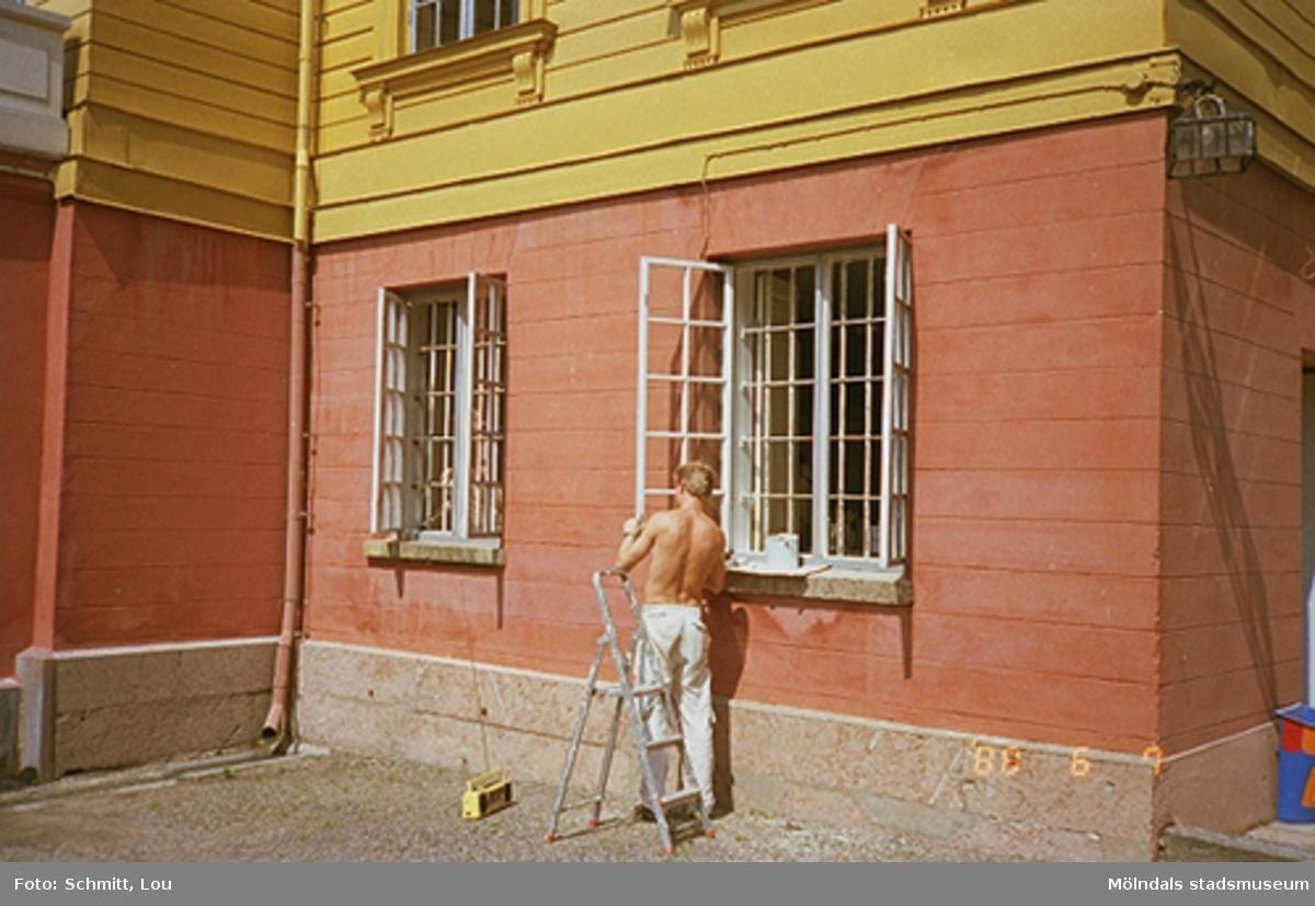 En man som målar ett fönster utomhus på Gunnebo slott.
