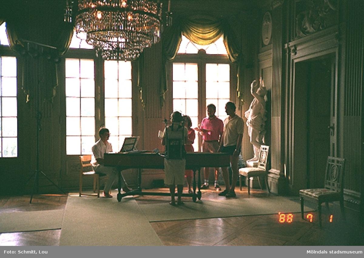 Fyra körsångare, med sånghäften i händerna, står framför en man som spelar på en flygel inne på Gunnebo slott. Bakom mannen ser man höga, stora fönster. I rummet finns en magnifik kristallkrona hängande i taket, två lindomestolar samt en skulptur. Väggarna är vackert dekorerade.