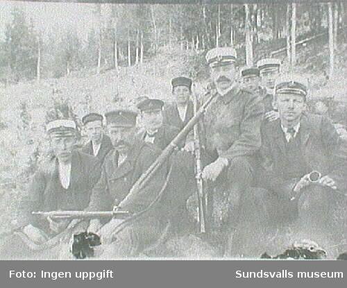 Män med gevär och uniformsmössor medSundsvalls vapen.