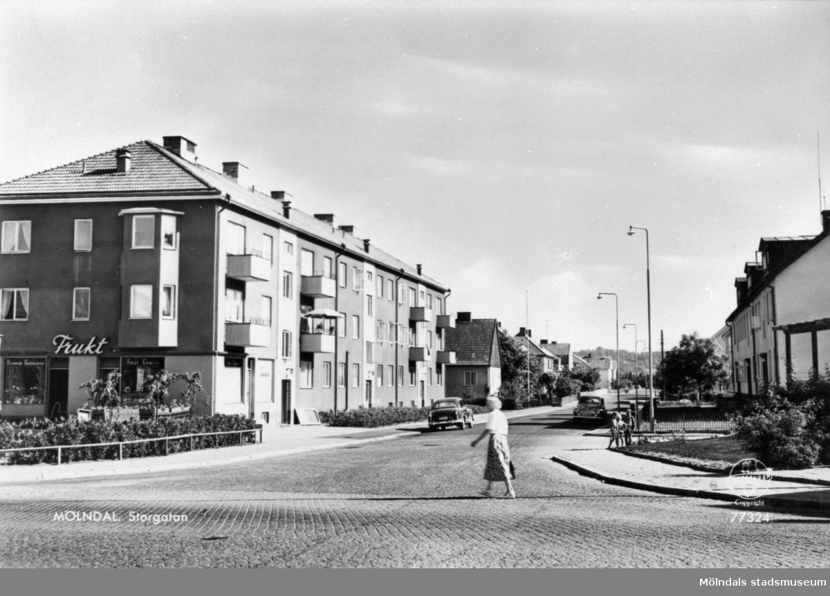 """Vykort """"Mölndal. Storgatan"""" från 1950-tal. Utsikt från Frölundagatan utefter Storgatan söderut. Till vänster (husets gavel) ligger Brogatan 23 (Berghedes Frukt & Blommor, Danskens bageri på hörnet, senare Järnhuset). Lägenheterna ligger på Storgatan 33A-C. Till höger skymtar Storgatan 34-36."""