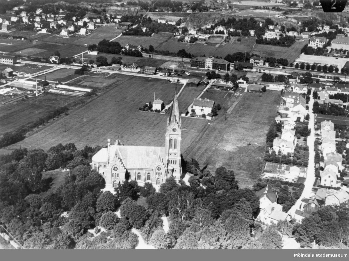 Flygfoto över det som nu är Mölndals centrum. I förgrunden ses Fässbergs kyrka. Till vänster ses trädgårdsmästeriet Annehill och till höger Bergmansgatan. I mitten ses Karlsberg (Knutsegatan 15, nuvarande Stadshusparken). Därovanför ses Svalöfsbolaget och Mölndals Nedre, i bakgrunden området Trädgården. 1930-1940-tal.