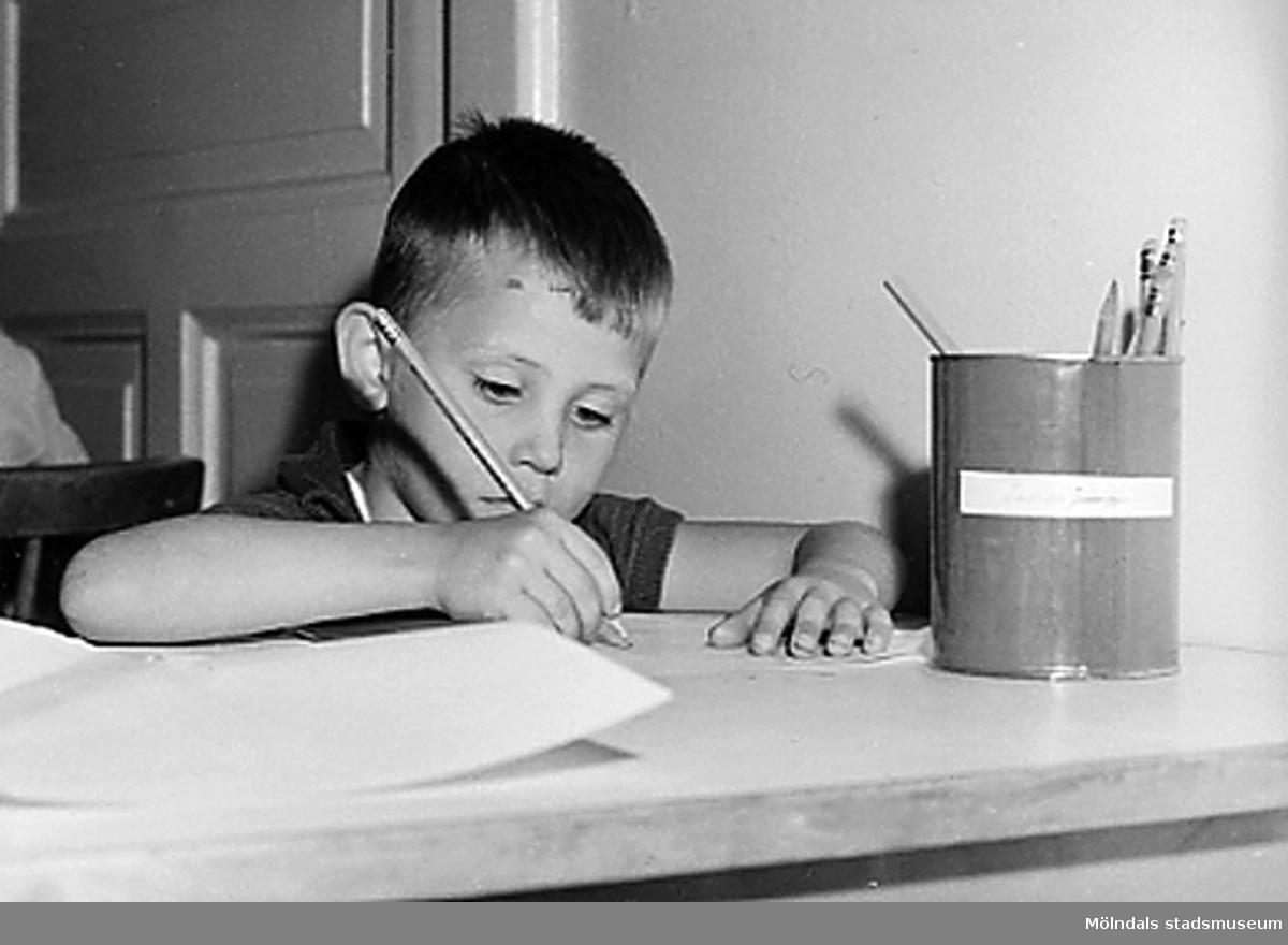 En pojke skriver på ett papper. Holtermanska daghemmet 1953.
