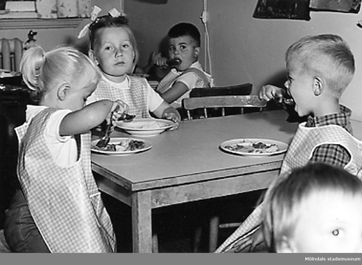 Barn sitter runt ett bord och äter i köket. Holtermanska daghemmet 1953.