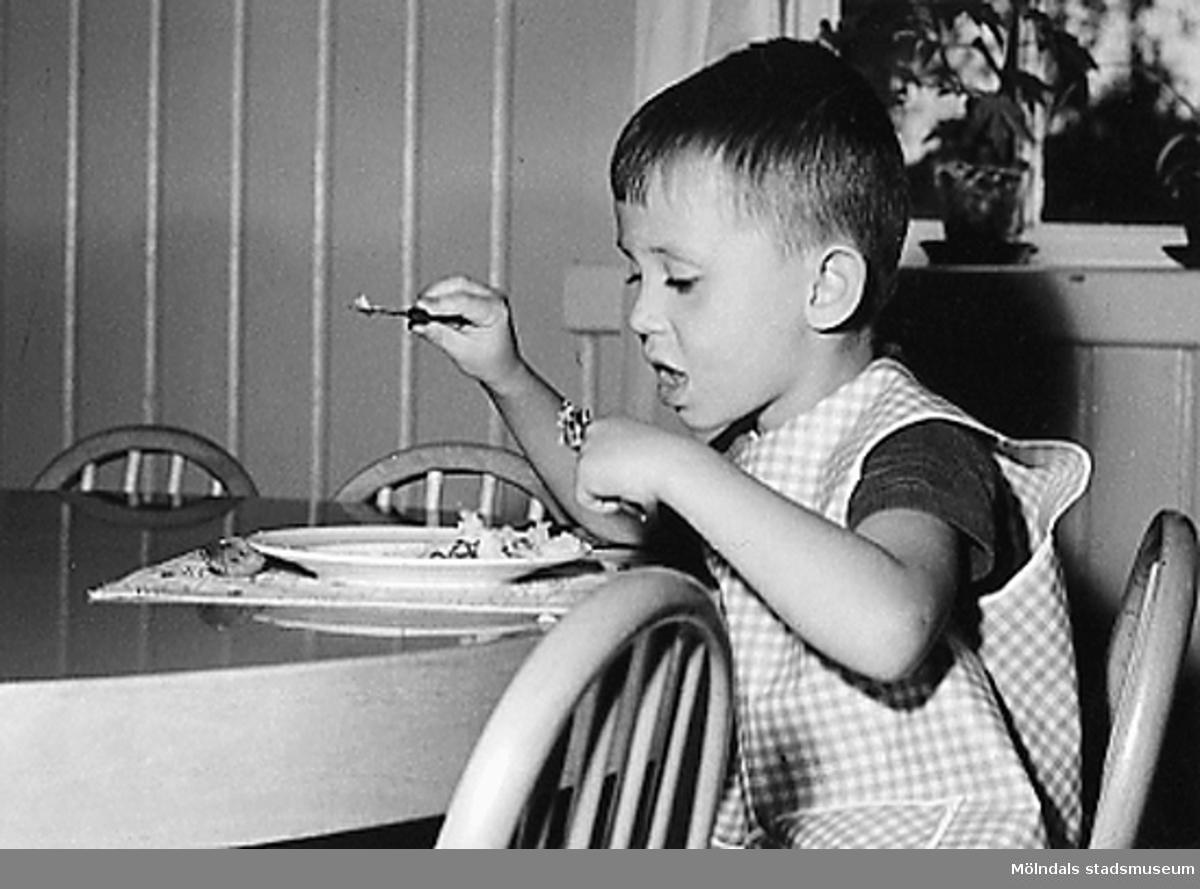 En pojke som äter mat på Holtermanska daghemmet 1953.