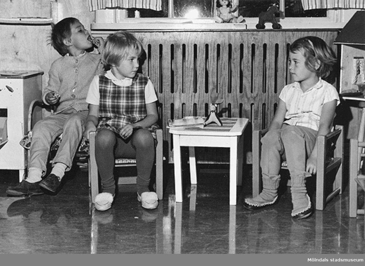 Tre barn sitter vid ett litet bord. Holtermanska daghemmet 1953.