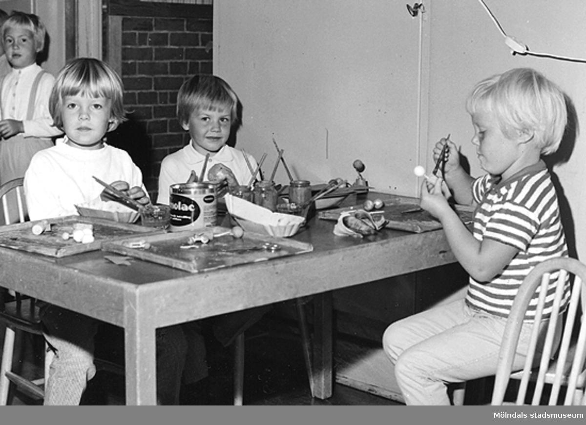 Några barn sitter och målar vid ett bord. Holtermanska daghemmet 1953.